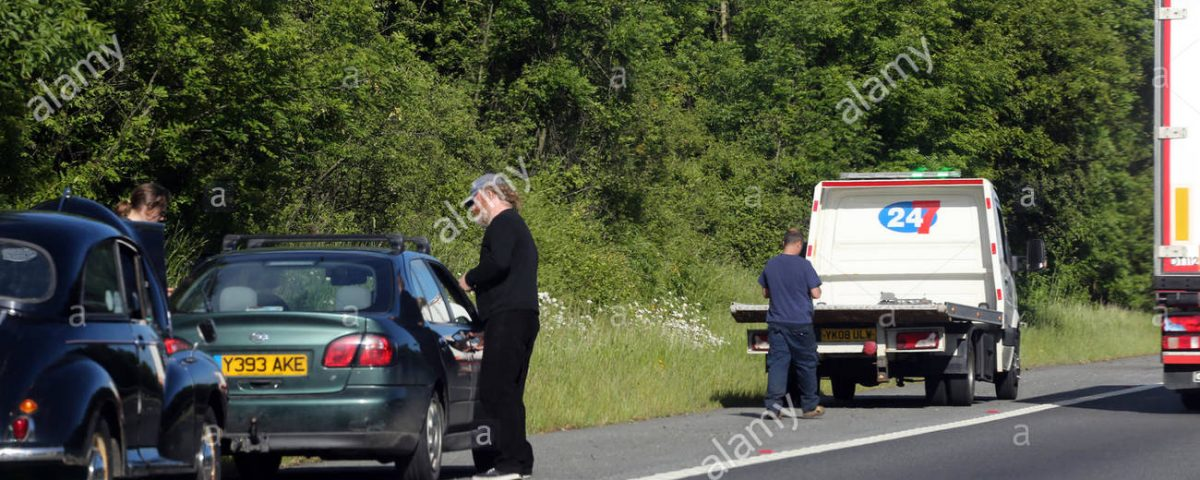 tow-truck-waiting-to-pick-up-car-after-breakdown-on-hard-shoulder-GFWPR7
